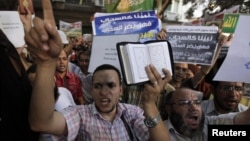 People shout and hold slogans in front of the U.S. embassy during a protest in Cairo, Egypt, September 11, 2012.