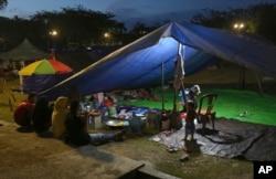 Perempuan mengobrol di dekat tenda di penampungan sementara di Palu, Sulawesi Tengah, 6 Oktober 2018. (Foto: AP)