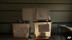 Completed ballots are inside boxes inside a polling station, during the first round of the parliamentary election, in the Imbaba district of Giza, near Cairo, Egypt, Monday, Oct. 19, 2015.