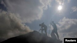 FILE - Palestinian workers rake a pile of wood as they make charcoal for sale, in the West Bank village of Yabed, June 11, 2014.