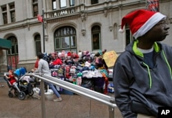 FILE - A New York street vendor waits for customers to buy his winter hats and sweatshirts on Christmas Eve in lower Manhattan's Zuccotti Park, Dec. 24, 2015.