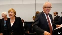 ນາຍົກ ລັດຖະມົນຕີ ເຢຍຣະມັນ ທ່ານນາງ Angela Merkel (ຊ້າຍ) ຍິ້ມແຍ້ມຂະນະທີ່ ຜູ້ນຳກຸ່ມພັກຝ່າຍ ທ່ານ Volker Kauder ເປີດກອງປະຊຸມ ຂອງພັກ Christian Democratic ກ່ອນມື້ ລົງຄະແນນສຽງ ກ່ຽວກັບ ການກອບກູ້ເສດຖະກິດຂອງກຣິສ ອີກຊຸດໜຶ່ງ ໃນວັນພຸດ ທີ 18 ສິງຫາ 2015.