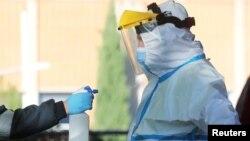Zdravstveni radnik u zaštitnoj opremi ispred hitne pomoći u bolnici u predgrađu Madrida (Foto: Rojters/Sergio Perez/Arhiva)