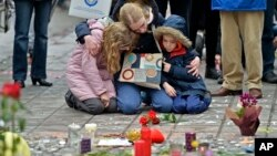 A woman and children sit and mourn for the victims of the bombings at the Place de la Bourse in the center of Brussels, Wednesday, March 23, 2016. (AP Photo/Martin Meissner)