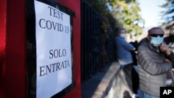 A directional sign at a COVID-19 testing site is seen near a growing line of test seekers in the northern Italian town of Bozen on Friday, November 20, 2020. (AP Photo/Antonio Calanni)