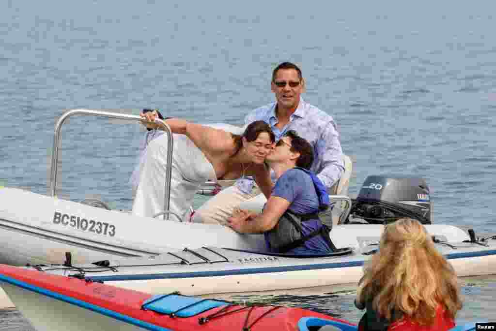 زوج کانادایی که عروسی خود را روی آب جشن می گرفتند با حضور نخست وزیر کانادا روبرو شدند و جاستین ترودو، عروس را در این عکس می بوسد.
