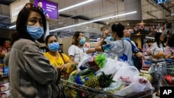 Shoppers wearing face masks with a cart full of food supplies wait in line to pay at a supermarket counter in Singapore, Tuesday, Mar. 17, 2020. (AP Photo/Ee Ming Toh)