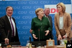FILE - German Chancellor Angela Merkel, second from left, arrives with North Rhine-Westphalia state governor Armin Laschet (L), Hesse state governor Volker Bouffier (2nd from R), and Julia Kloeckner (R) for a board meeting of her Christian Democratic Union party at the headquarters in Berlin, Nov. 27, 2017.