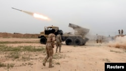 FILE - Iraqi soldiers fire a rocket toward Islamic State militants on the outskirt of the Makhmour south of Mosul, Iraq, March 25, 2016.