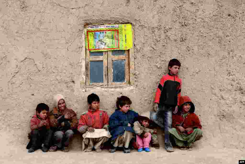 Afghan children sit near their home in Herat. As winter sets in across Central Asia, many Afghans struggle to provide adequate food and shelter for their families.