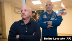 In this March 26, 2015 file photo, U.S. astronaut Scott Kelly, right, crew member of the mission to the International Space Station, stands behind glass in a quarantine room, behind his brother, Mark Kelly, also an astronaut, after a news conference (AP Photo/Dmitry Lovetsky)