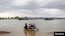Phụ nữ và trẻ em sơ tán trên chiếc thuyền con sau khi bão Haiyan ập vào tỉnh Quảng Ninh, cách Hà Nội 180 km ngày 11/11/2013. 13 người thiệt mạng. REUTERS/Kham
