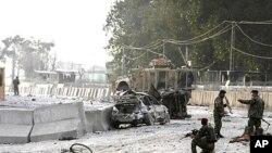 ພວກທະຫານອັຟການິສຖານ ຮັກສາຄວາມປອດໄພ ຢູ່ບ່ອນເກີດເຫດວາງລະເບີດສະລະຊີບ ທີ່ທາງເຂົ້າ ສະໜາມບິນເມືອງ Jalalabad, ແຂວງ Nangarhar ໃນພາກຕາເວັນອອກຂອງອັຟການິສຖານ, ວັນທີ 27 ກຸມພາ 2012.