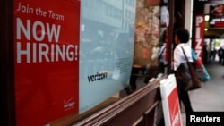 "FILE - A ""Now Hiring"" sign is posted on a Verizon store in Manhattan in New York City, May 10, 2016."