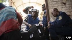 Des membres de la Commission électorale nationale indépendante (CENI) chargent un camion avec le matériel de vote qui sera distribué de l'entrepôt de la CENI à divers bureaux de vote à Bukavu, le 28 décembre 2018.