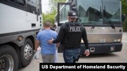 Yon polis imigrasyon ameriken kap eskòte yon imigran ki komèt yon krim sou teritwa ameriken an e ki sou depòtasyon. Foto: April 3, 2019.