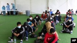 FILE - In this March 30, 2021, young migrants wait to be tested for COVID-19 at the Donna Department of Homeland Security holding facility, the main detention center for unaccompanied children in the Rio Grande Valley, in Donna, Texas.
