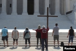 Demonstrators gather outside the U.S. Supreme Court as the court ruled that religious institutions like churches and schools are shielded from employment discrimination lawsuits in Washington, July 8, 2020.
