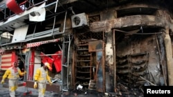 Bağdat'ın Karrada mahallesindeki bombalı saldırı sonrası temizlik yapan belediye işcileri