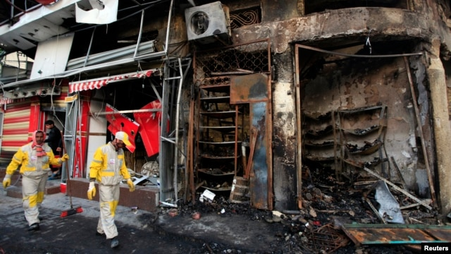 Municipal workers clean the site of a bomb attack in Baghdad's Karrada district, Feb. 18, 2014.