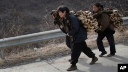 North Korean women carry firewood as they walk along a highway in Sinpyong county in North Hwanghae province, North Korea. There are concerns that new sanctions will hurt ordinary North Koreans.