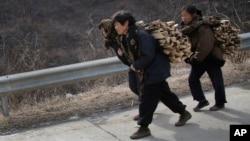 Phụ nữ Bắc Triều Tiên vác củi dọc đường cao tốc ở quận Sinpyong, tỉnh Hwanghae, ngày 19/2/2016. Người dân vô tội đang nếm trải những khó khăn về kinh tế từ hậu quả của các biện pháp chế tài quốc tế lên Bắc Triều Tiên.