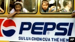Trẻ em trên một chiếc xe bus có sơn hình ảnh quảng cáo đồ uống có ga của Mỹ ở Hà Nội trong tấm ảnh chụp cuối những năm 1990. Sau khi Mỹ và Việt Nam thiết lập lại quan hệ ngoại giao năm 1995, các công ty Mỹ đã đổ vào Việt Nam để đầu tư và kinh doanh.