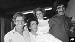 FILE - From left, actors Harrison Ford, Anthony Daniels, Carrie Fisher and Peter Mayhew take a break on the set of a 1978 television special.