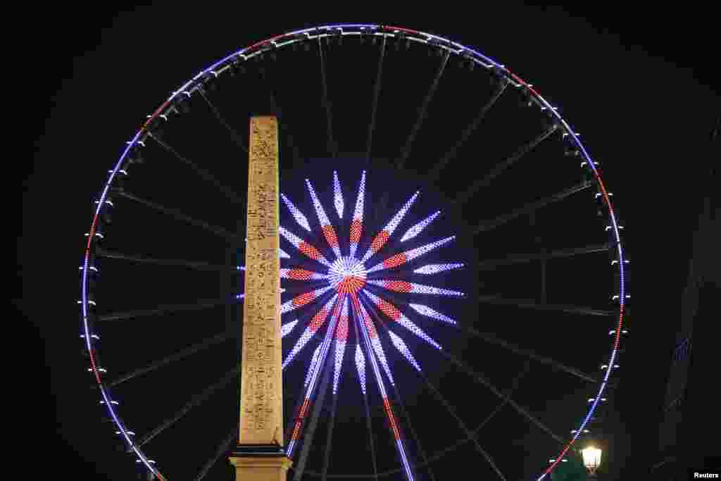 A giant Ferris wheel fills the Paris skyline with blue, white and red lights behind the Luxor Obelisk at the Place de la Concorde in central Paris, France.