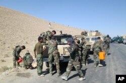 Members of Afghan security forces and volunteer militias break on their way to Kunduz, Afghanistan, to fight against Taliban militants, Oct. 1, 2015.