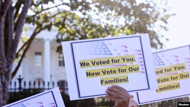 Pancartas que reclaman al presidente cumplir lo prometido frente a la reforma migratoria.