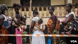 Des mères et leurs enfants font la queue pour voter dans un bureau à Freetown, en Sierra Leone, le 7 mars 2018. (VOA/Jason Patinkin)
