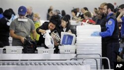 Travelers at John F. Kennedy International Airport in New York go through security screening, 22 Oct 2010