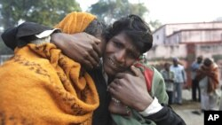 An Indian man whose two relatives died in a stampede at a railway station cries and comforts other relative as they arrive to take the bodies from a morgue, in Allahabad, India, February 11, 2013.