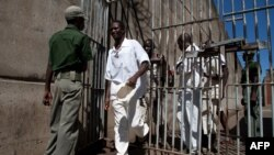 Des détenus de la prison passent devant un gardien de prison à la prison de sécurité maximale de Chikurubi à Harare, Zimbabwe le 20 mai 2015