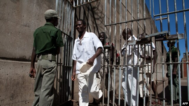 FILE - Prison Inmates walk past a prison guard at the Chikurubi Maximum security prison in Harare, Zimbabwe, May 20, 2015 during a tour by a parliamentary committee to assess the state of the nation's prisons where inmates widely complained of food shortages, over-crowding and inadequate food rations and diet.