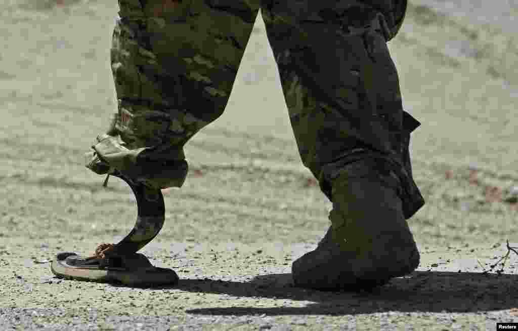 A NATO soldier walks with an artificial limb to board a Chinook helicopter after a security handover ceremony at a military academy outside Kabul, Afghanistan.