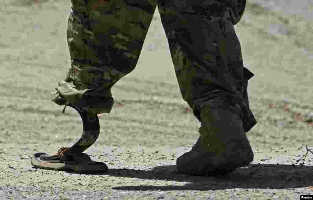 Seorang tentara NATO berjalan dengan kaki palsu menuju helikopter, setelah upacara serah terima keamanan dari pasukan NATO kepada pasukan Afghanistan di luar ibukota Kabul.