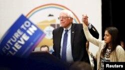 Bernie Sanders levanta la mano de una joven inmigrante durante el cabildo abierto en el casino Nación Navajo en Flagstaff, Arizona.
