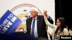 버니 샌더스 미 민주당 대선 후보가 17일 애리조나주 플래그스태프에서 열린 유세에서 이민 청소년 운동을 이끄는 캐서린 부에노 양의 손을 들어주고 있다.
