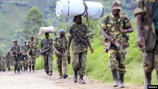 M23 rebel fighters walk as they withdraw near the town of Sake, west of Goma in eastern Congo, November 30, 2012.