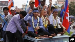 Anti-government protesters who had been in prison since their arrest in January, wave from atop a truck during a rally, in Phnom Penh, file photo.