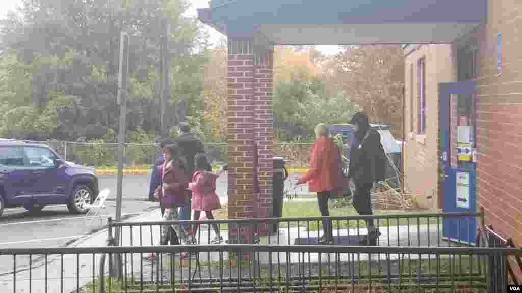 许多选民带着孩子冒大雨来投票站投票。据悉,本次投票率比往届高了不少。有人估计这个选区的投票率可能高达80%。(美国之音魏之拍摄)