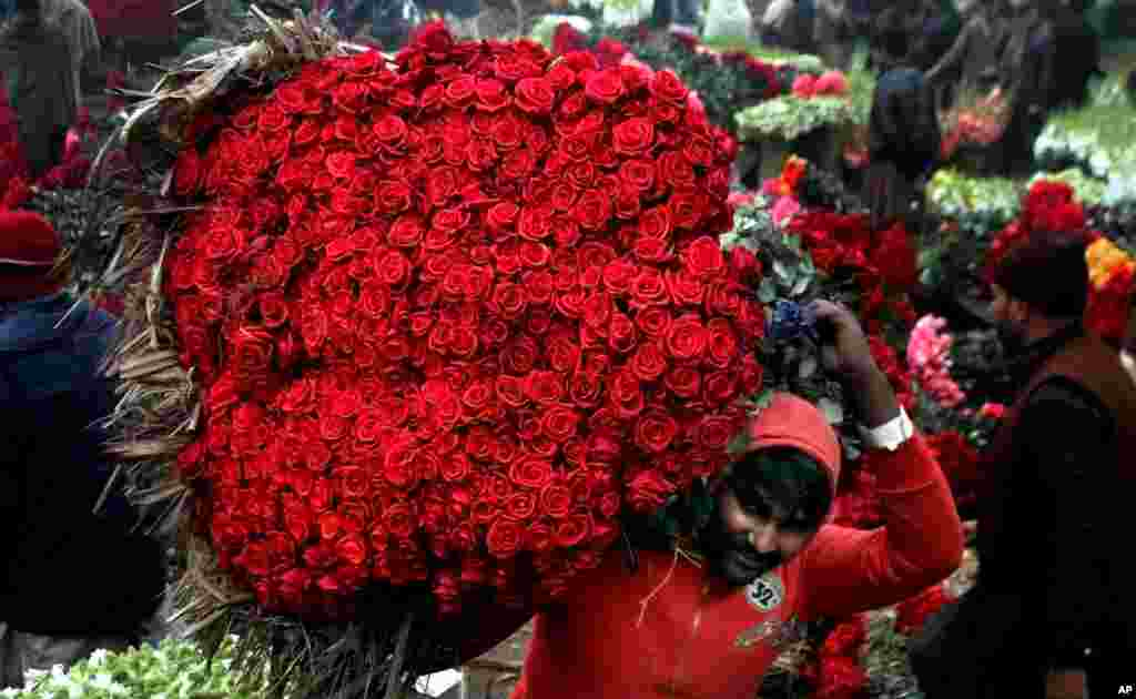 A laborer carries a bundle of red roses at a wholesale flower market in Lahore, Pakistan.