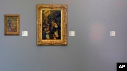 "FILE - The empty space where Henri Matisse' painting ""La Liseuse en Blanc et Jaune"" was hanging, right, is seen next to a painting by Maurice Denis, center, and Pierre Bonnard, left, at Kunsthal museum in Rotterdam, Netherlands, Oct. 16, 2012."
