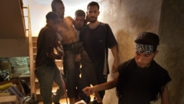 Syrian rebels carry a wounded comrade into a secret field hospital in al-Bab, northeast of Aleppo, August 10, 2012.