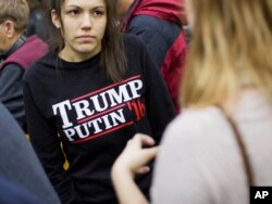 "FILE - A woman wears a shirt reading ""Trump Putin '16"" while waiting for Republican presidential candidate Donald Trump to speak at a campaign event at Plymouth State University in Plymouth, New Hampshire, Feb. 7, 2016."