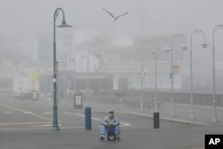 A street performer sits alone at Fisherman's Wharf in San Francisco, March 12, 2020. Gov. Gavin Newsom said sweeping guidance for Californians to avoid unnecessary gatherings to prevent the spread of coronavirus will likely extend beyond March.
