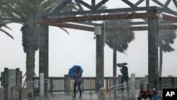 Los amantes de la playa fueron sorprendidos por lluvias torrenciales asociadas con la tormenta tropical Colin en Clearwater Beach, Florida, el lunes, 6 de junio de 2016.