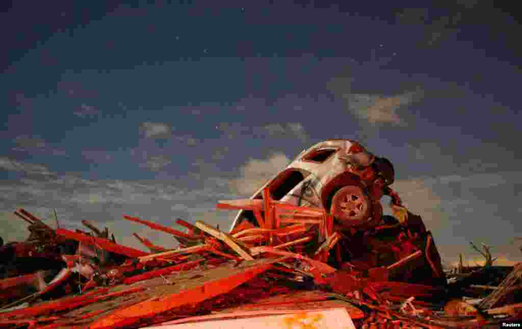 A vehicle sits on a pile of debris from the destruction caused by a tornado that touched down in Washington, Illinois, USA, Nov. 17, 2013.